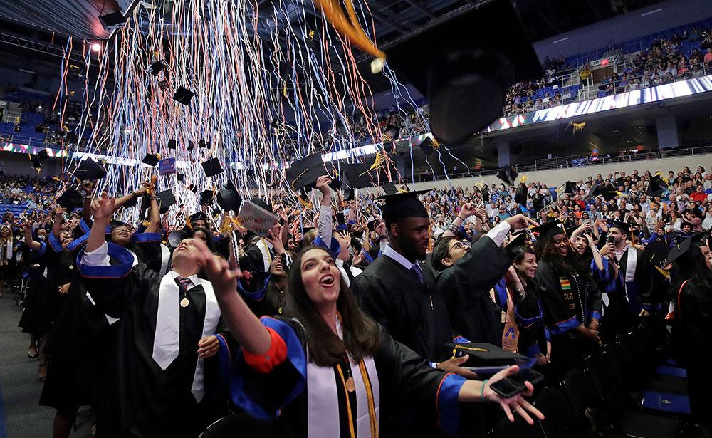 large group celebrating graduation in College Park Center