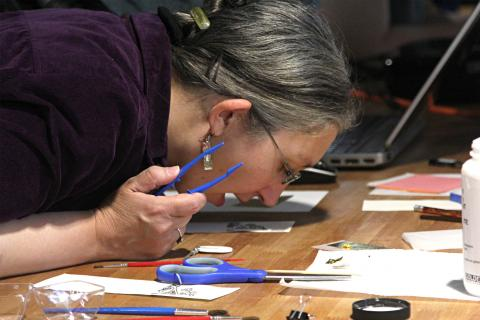 Kathryne Beebe, assistant professor of medieval history and digital humanities, breathes on a gesso design.