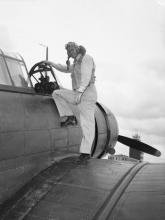 Second Lieutenant Hugh E. Munnell of Dallas, Texas, climbing into his bomber at the Marine Air Base, Eagle Mountain Lake, on Apr