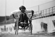 Black and white image of Jim Hayes worked hard to push a track chair into a stadium.