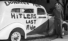 Man standing in front of car with hand painted letters: Donated for Hitler's Last Ride