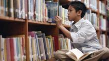child pulling book from shelves