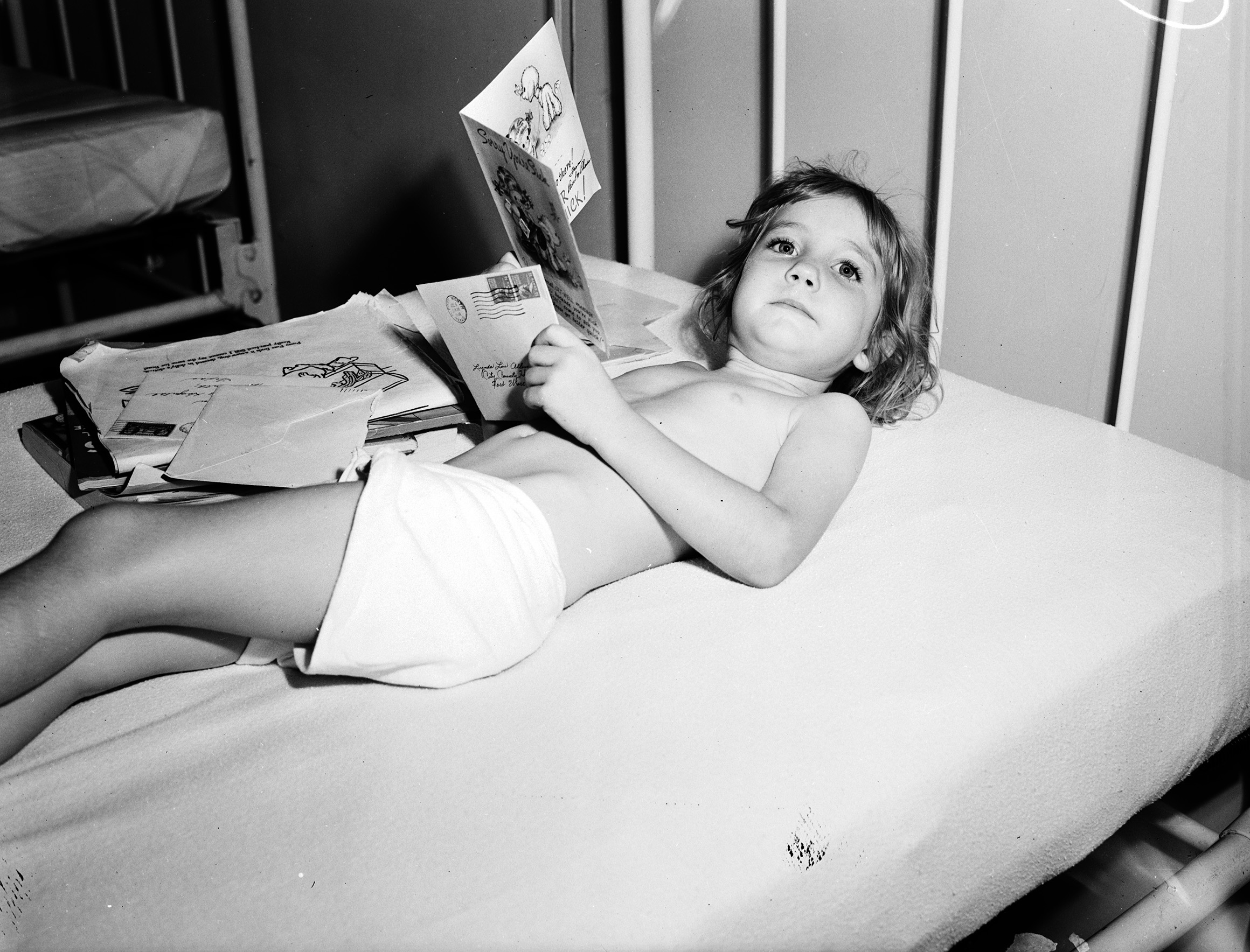 unidentified child with polio reads get well cards while laying in