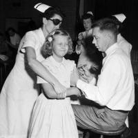 Doctor and nurse giving child polio vaccine