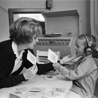 speech therapist works with boy wearing headphones