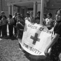 students holding the green cross flag for safety