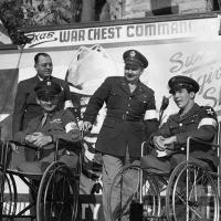 Three men in uniform, two of whom are paraplegics in wheelchairs