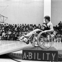 Student shows athletic prowess with his wheelchair in front of group of high school students