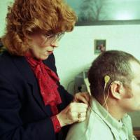 woman hooking up a cochlear implant for man