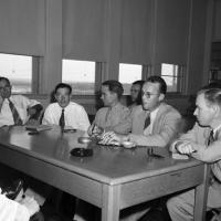 men in suits and ties sitting around a table