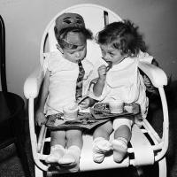 two toddlers sitting in a chair