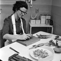 woman learns how to peel a potato in a special-equipment kitchen at rehabilitation center