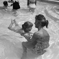 blind child learns to swim with the assistance of an adult aid