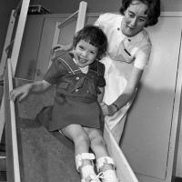 Girl enjoys a slide with physical therapist assisting