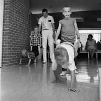 physical therapist works with boys battling cystic fibrosis to assist them with wheelbarrow exercise