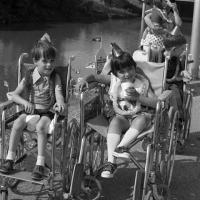 children seated in wheelchairs and wearing party favors alongside the Trinity River