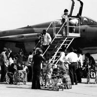 children, some in wheelchairs, are given a tour of an airplane