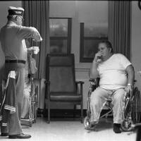 man sitting in a wheelchair and smoking a cigarette while listening to another man talk