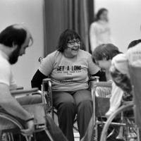 a group of adults in wheelchairs are laughing