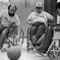 group of people in wheelchairs go after a ball