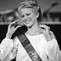 A young woman is wearing a sash that says Miss Houston.