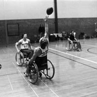 college students play wheelchair football in a high school gymnasium