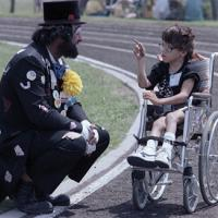 Wheelchair race competitor talks with a clown at the regional Special Olympics games