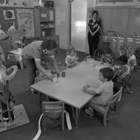 toddlers sitting around a short table with two adults in the classroom
