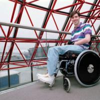 Craig Crosby poses in a wheelchair beside a window with an airplane