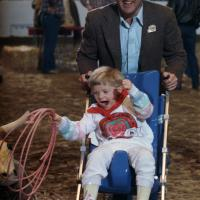 Rodeo for disabled children; cowboy Brad Barnes gives Chanin Aiken a push