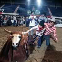 Rodeo for disabled children; cowboy Ron Lewis helps Chris Doss rope a fake steer