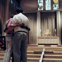 two people embracing in church