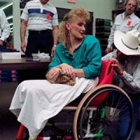 Renea Watson getting her wheelchair autographed by George Strait