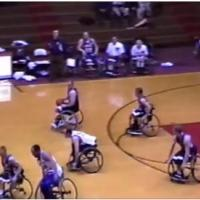 6 men in wheelchairs playing basketball and 4 people on sideline