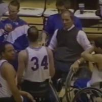 coach with players at wheelchair basketball game
