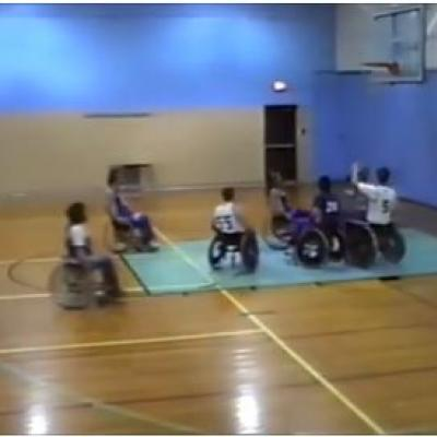 6 men in wheelchairs playing basketball