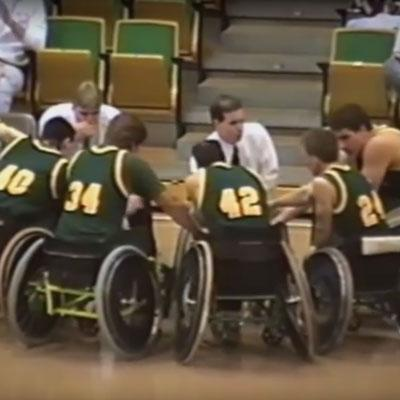 wheelchair basketball players in huddle with coaches